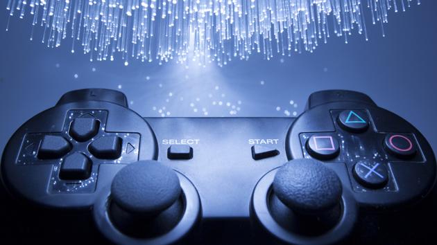 Nahaufnahme eines Gamecontrollers vor einem blauen Hintergrund mit Lichteffekten