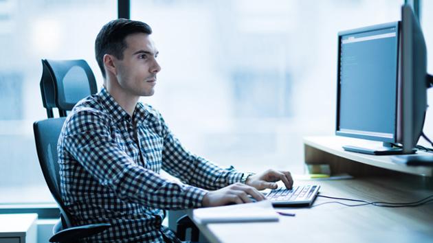 Ein Mann in kariertem Hemd sitzt konzentriert vor zwei Computer-Bildschirmen und tippt auf seiner Tastatur.