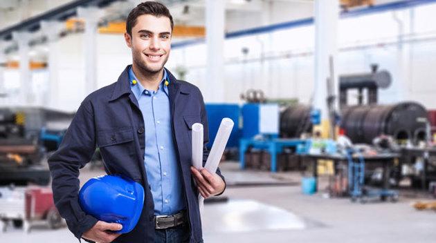 Ein Facharbeiter steht mit seinem Schutzhelm in der Hand in einer Werkstatt.