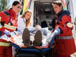 Eine Rettungssanitäterin, ein Notfallsanitäter und eine Notärztin kümmern sich um einen Patienten.