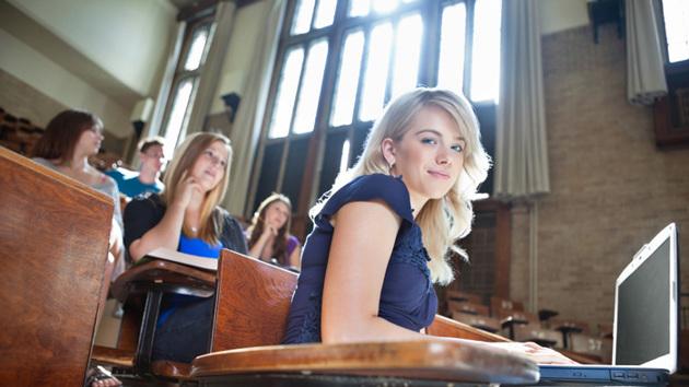 Eine Studentin sitz in einem vollen Hörsaal an ihrem Laptop und lächelt.