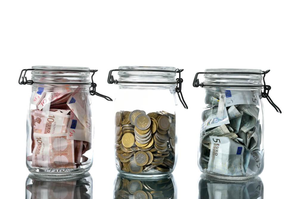 Drei transparente Einmachgläser mit unterschiedlich vielen Euros befüllt.