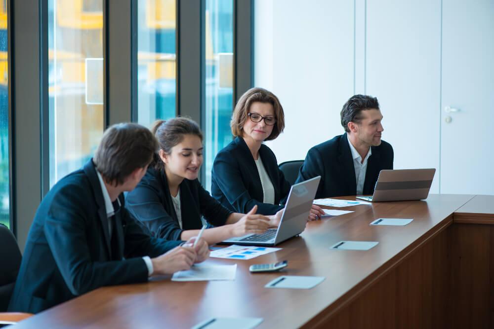 Mehrere Wirtschaftsprüferinnen und Wirtschaftsprüfer besprechen sich in einem Meeting-Raum.