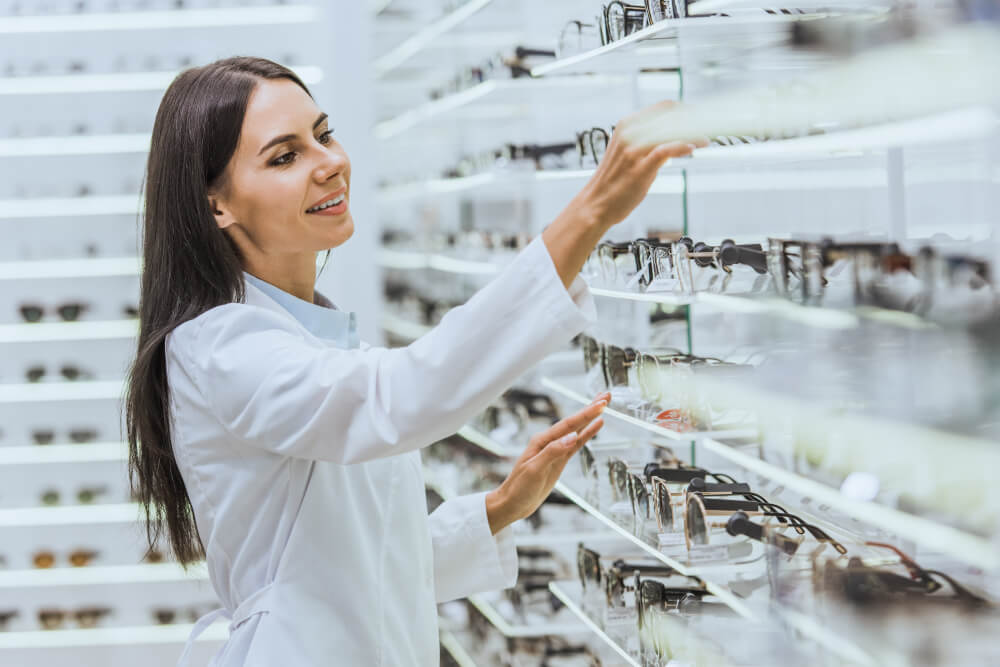 Eine Augenoptikerin sortiert eine Brille ins Verkaufsregal ein
