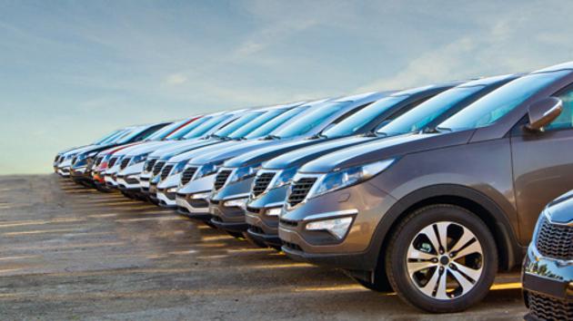 Mehrere Firmenwagen stehen aufgereiht auf einem Parkplatz.