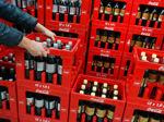 Ein Mitarbeiter stapelt Coca-Cola-Kisten in einem Getränke-Lager.