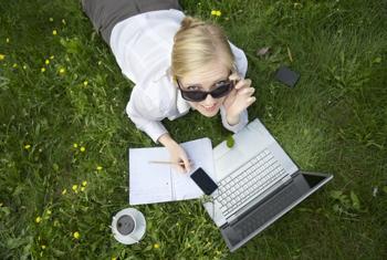 Frau arbeitet draußen am Laptop