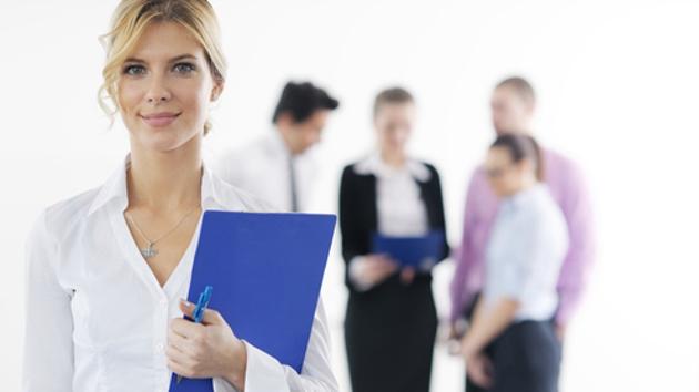 Eine Chefin steht mit einem Notizblock und Stift vor ihren Angestellten.