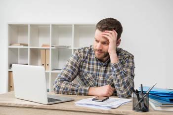 Ein junger Freiberufler sitzt mit sorgenvollem Gesicht vor seinem Computer.