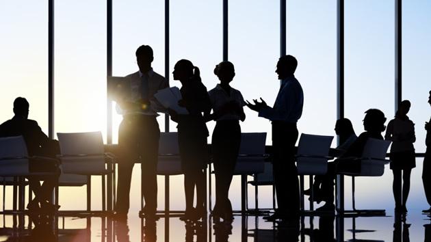Führungskräfte stehen an einem Verhandlungstisch in einem Büro und beraten sich.