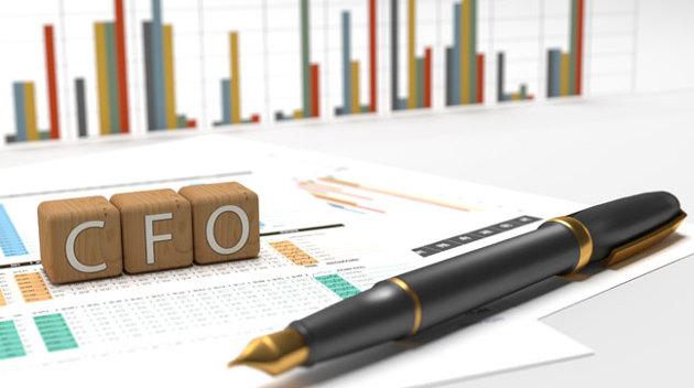 Ein Füller liegt auf Unterlagen mit bunten Statistiken vor Holzwürfeln mit der Aufschrift CFO.