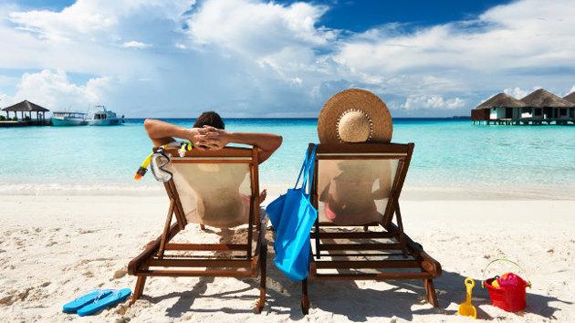 Zwei Urlauber liegen auf Strandliegen an einem türkisblauen Meer.