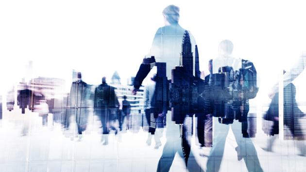 Eine Gruppe von Geschäftsleuten läuft in Richtung einer Skyline.