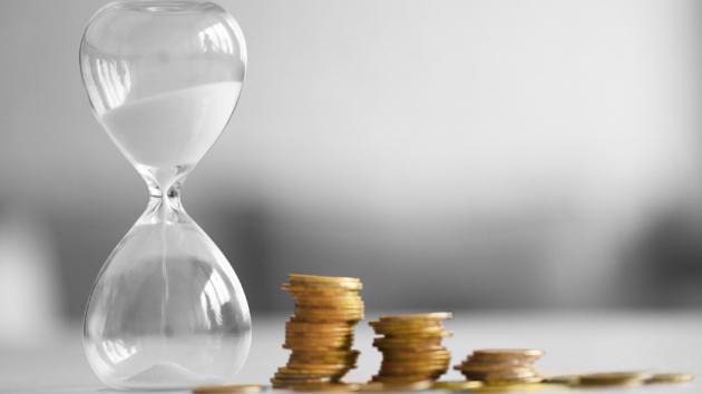 Nach der Höhe in absteigender Reihenfolge gestapelte Geldmünzen stehen neben einer Sanduhr.