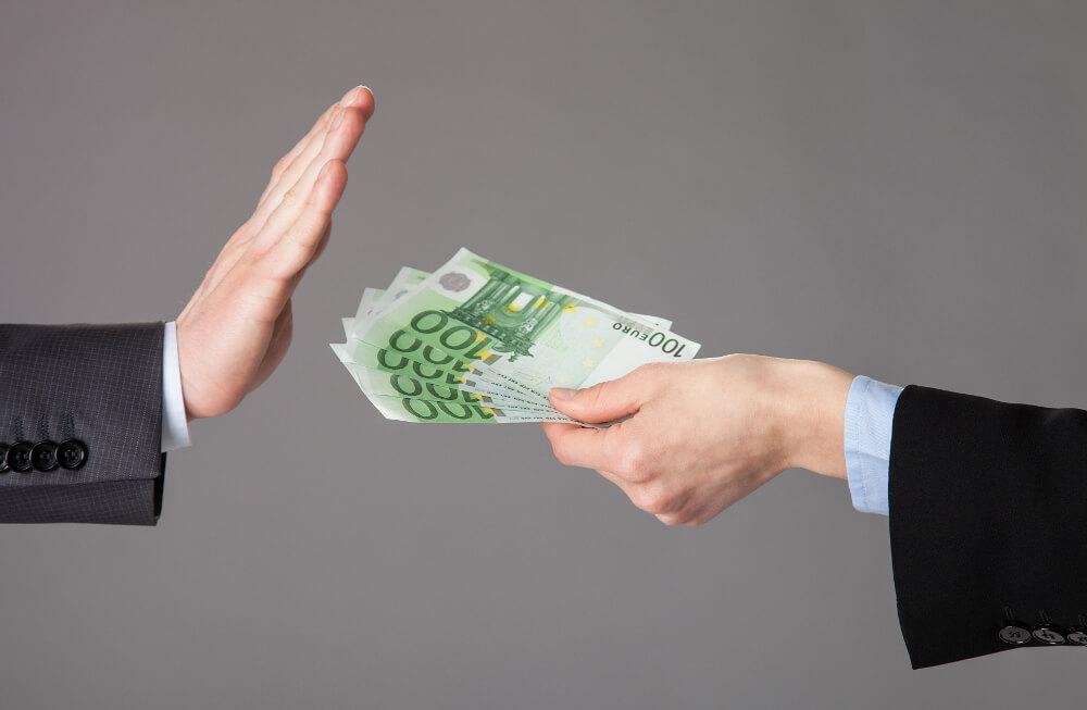 Ein Mann verzichtet mit einer ablehnenden Geste auf ihm angebotenes Geld.
