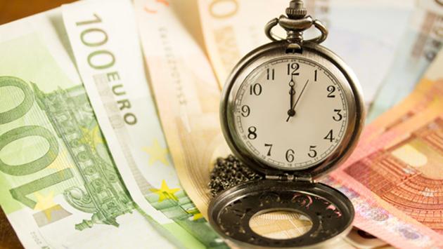 Eine Taschenuhr liegt auf Euroscheinen.