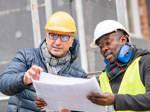 Zwei Männer betrachten auf der Baustelle gemeinsam einen Bauplan.