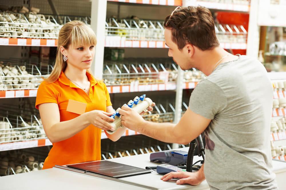Eine junge Baumarkt-Mitarbeiterin berät einen Kunden.