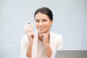 Frau mit Geld und Laptop am Tisch