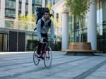 Fahrradkurier mit schwarzer Rückentasche fährt an einem Bürogebäude entlang.