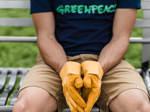 Ein Mann mit einem Greenpeace T-Shirt und gelben Arbeitshandschuhen sitzt auf einer Parkbank.
