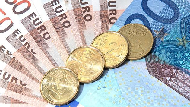 Mehrere aufgefächerte Euro-Scheine und Cent-Münzen