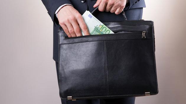 Eine Person zieht einen 100-Euro-Schein aus einer Businesstasche.