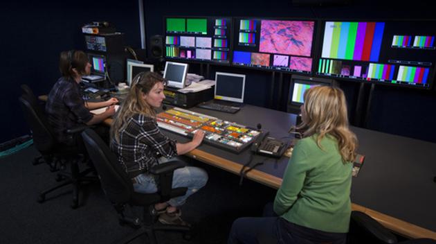 Drei Personen sitzen an einem langen Schreibtisch in einem dunklen Raum vor technischen Geräten und Bildschirmen.
