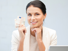 Eine Frau hält einen 50-Euro-Schein in der Hand und lächelt.