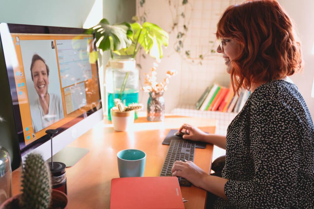 Frau sitzt lächelnd an einem Monitor und spricht mit einem Mann über einen Videochat