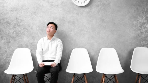 Ein Mann in weißem Hemd sitzt auf einem Stuhl vor einer grauen Wand und schaut nach oben.