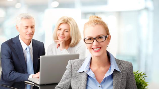 Eine Frau in Berufskleidung sitzt vor zwei am Laptop arbeitenden Personen und lächelt.