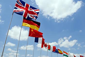 Flaggen verschiedener Länder wehen vor einem blauen Himmel