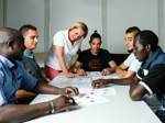 Eine Gruppe junger Flüchtlinge erlernt gemeinsam bei einem Sprachkurs die deutsche Sprache.