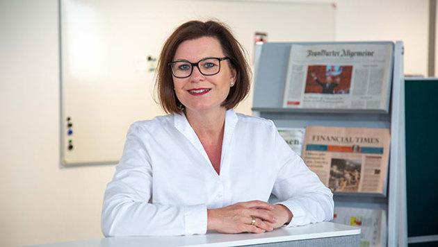 Marion Weckes, ehemalige Vergütungsexpertin der Hans-Böckler-Stiftung sitzt vor Zeitungen und lächelt.