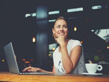 Frau sitzt am Laptop und lächelt