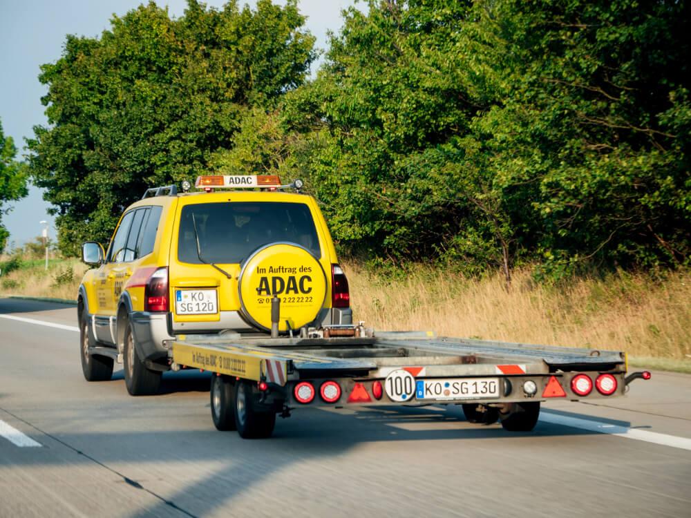 Ein Geländewagen des ADAC fährt mit einem leeren Anhänger auf einer Landstraße.
