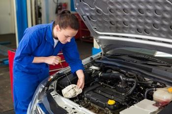 Kfz-Mechatronikern prüft Ölstand an einem Auto