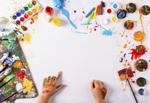 Ein kreativer Arbeitsplatz mit bunten Wasserfarben und Stiften rund um ein wießes Blatt Papier
