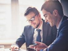 Zwei Männer in Anzügen sitzen gemeinsam am Schreibtisch und lächeln.