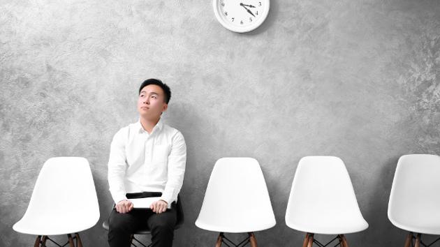 Ein Mann sitzt allein in einem Warteraum und hat seinen Blick nach oben gerichtet.
