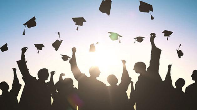 Mehrere Studienabsolventen werfen ihre Doktorhüte in die Luft.