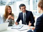 Mehrere junge Unternehmensberater und -beraterinnen tauschen sich in einem Meeting aus.