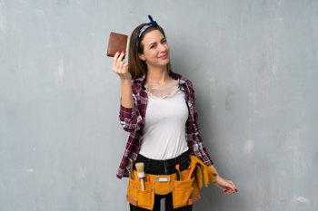 Eine junge Handwerkerin mit Werkzeuggürtel hält erfreut ein Portemonnaie in die Höhe.