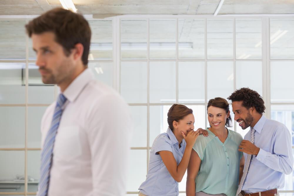 Ein Mann und zwei Frauen lästern über einen männlichen Arbeitskollegen.