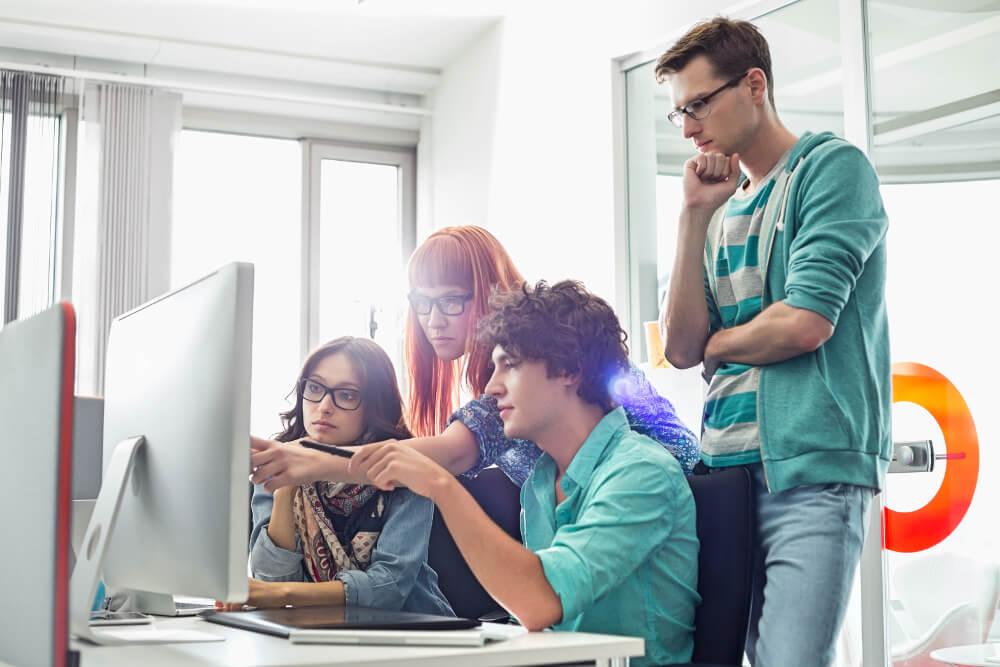 Junge Auszubildende betrachten gemeinsam einen Computer-Bildschirm.