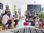 Viele junge, kreativ aussehende Menschen tummeln sich in einem Co-Working-Space.
