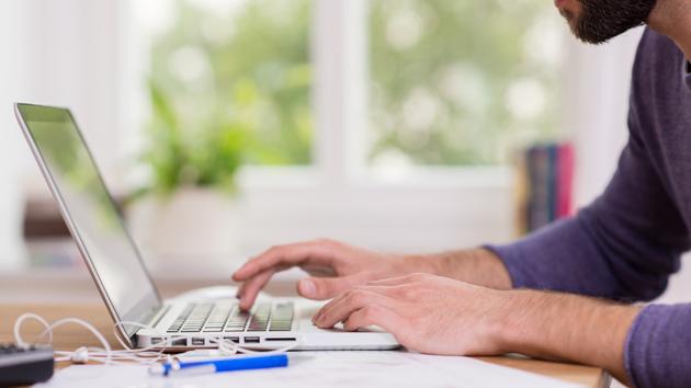 Ein Mann nimmt am Laptop an einer Umfrage teil.