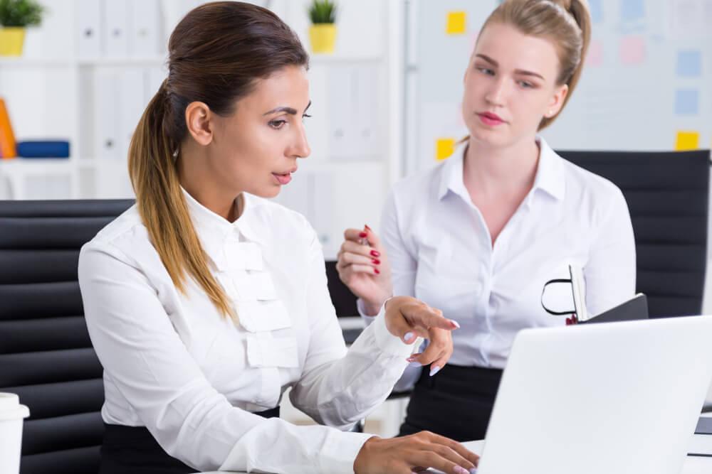 Eine junge Bewerberin sitzt beim Probearbeiten mit einer Mitarbeiterin vor einem Rechner