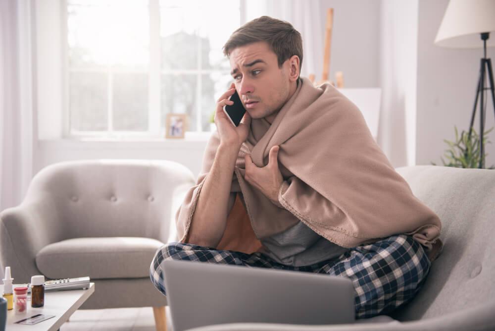 Ein krank aussehender Mann sitzt auf dem Sofa und telefoniert.